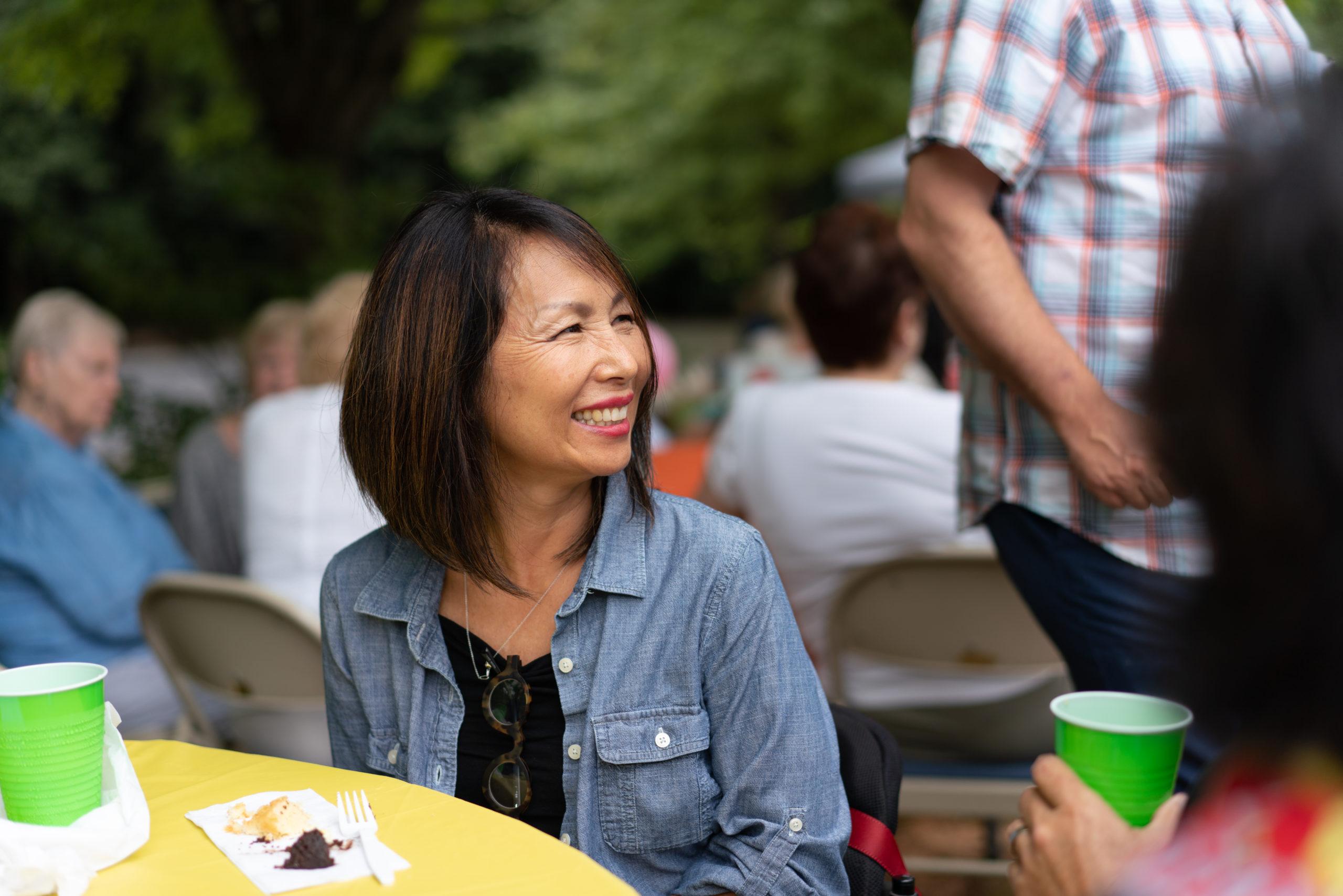Woman in denim jacket smiling at church picnic