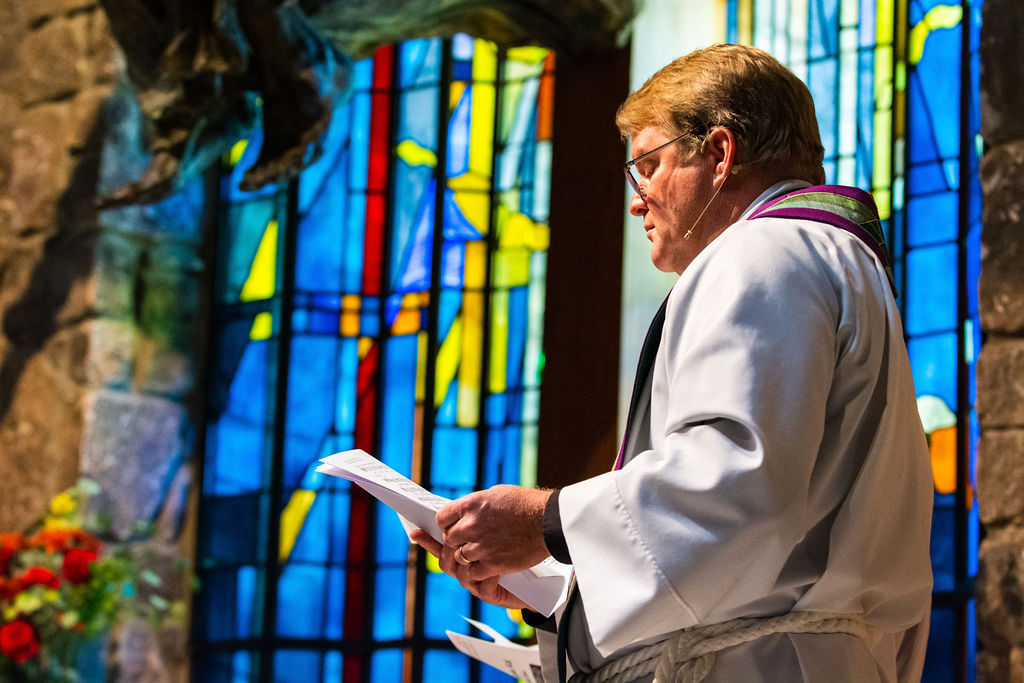 Rev. Richard Game reading from a sheet of paper during a church service