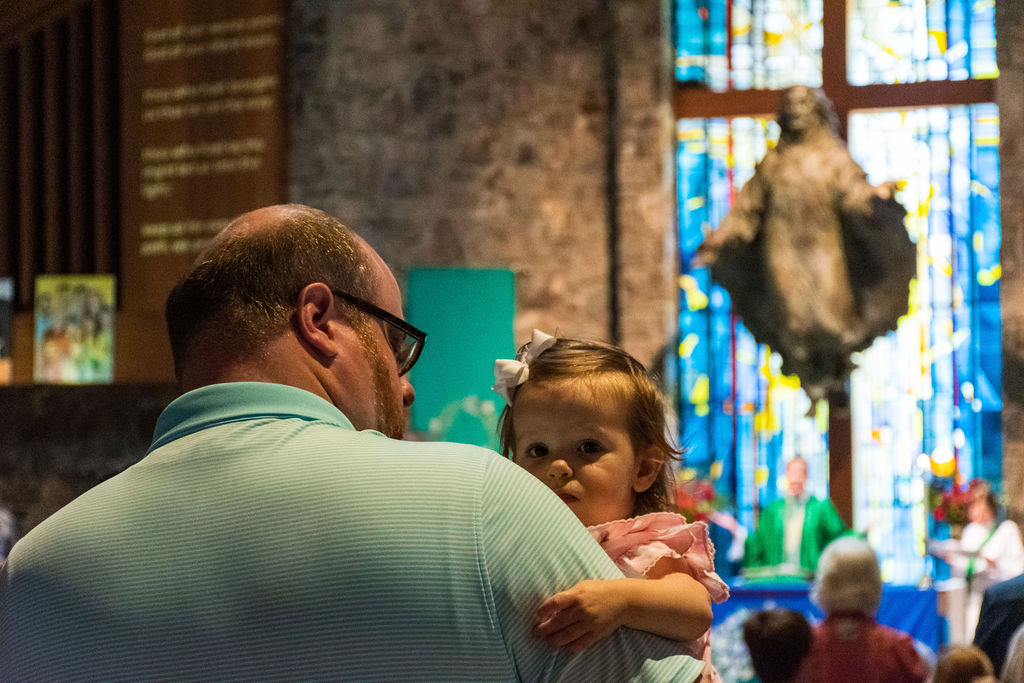 Father holding his toddler-age daughter during a worship service
